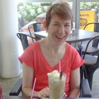 smiling lady enjoying a milkshake