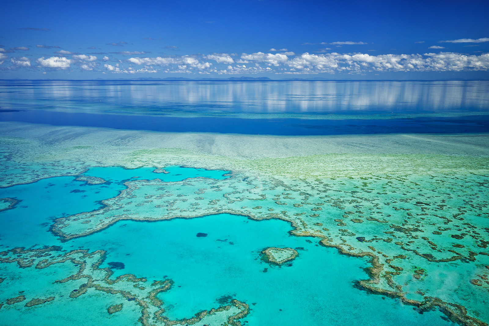 Arial view of the great barrier reef (outer reef) in the Whitsunday islands Queensland on a still and sunny day.